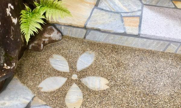 階段のディテール。自然石と洗い出し、敷石とシダの緑、そして桜の花びらが来客をもてなす。