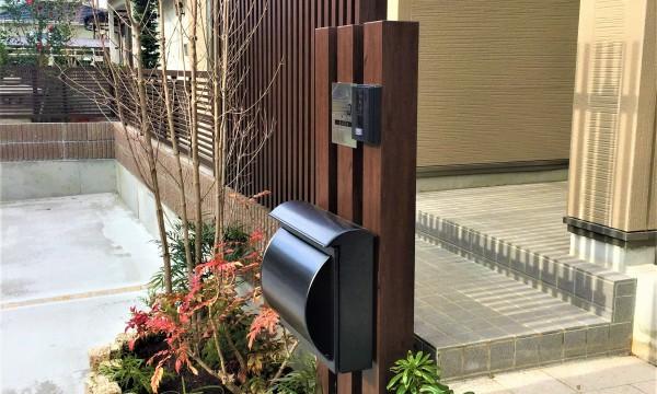 アプローチと門柱周りの仕上がり。門柱もフェンスと同じ色の角材を使用し、ブロック塀と駐車場コンクリートがメインとなるので葉色の鮮やかな樹木を植栽しました。