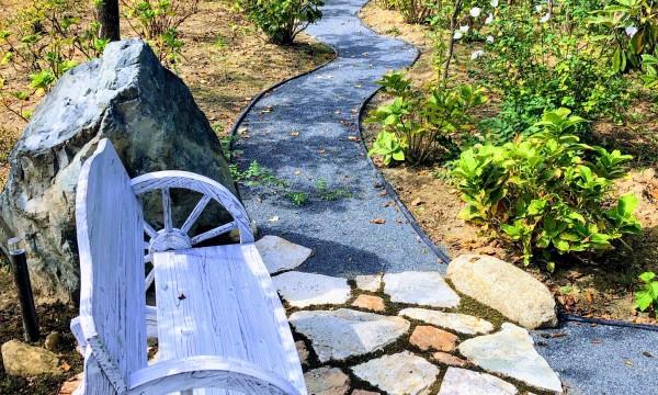 「ナチュラルガーデン」の小道に設けたベンチ。自然石の隙間に苔を縁取り、ベンチからはバラのアーチが眺められます。